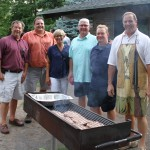 In the photo above  (left to right). town supervisor John Moffitt, town councilman Tom DuBois, town councilwoman Cynthia Carroll, town councilman Mike Roberts, town clerk Jim Merzke and town highway superintendent Bud Smith gather around this grill at the annual town Republican Party picnic. Photo by Peter Carosa
